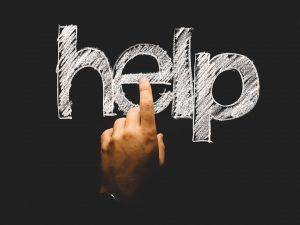 Schoolbord met letters help en iemand die wanhopig zijn vinger opsteekt
