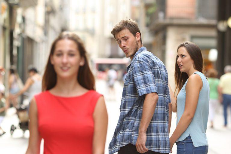 man en vrouw hand in hand, man kijkt naar andere vrouw en krijgt kwade blik