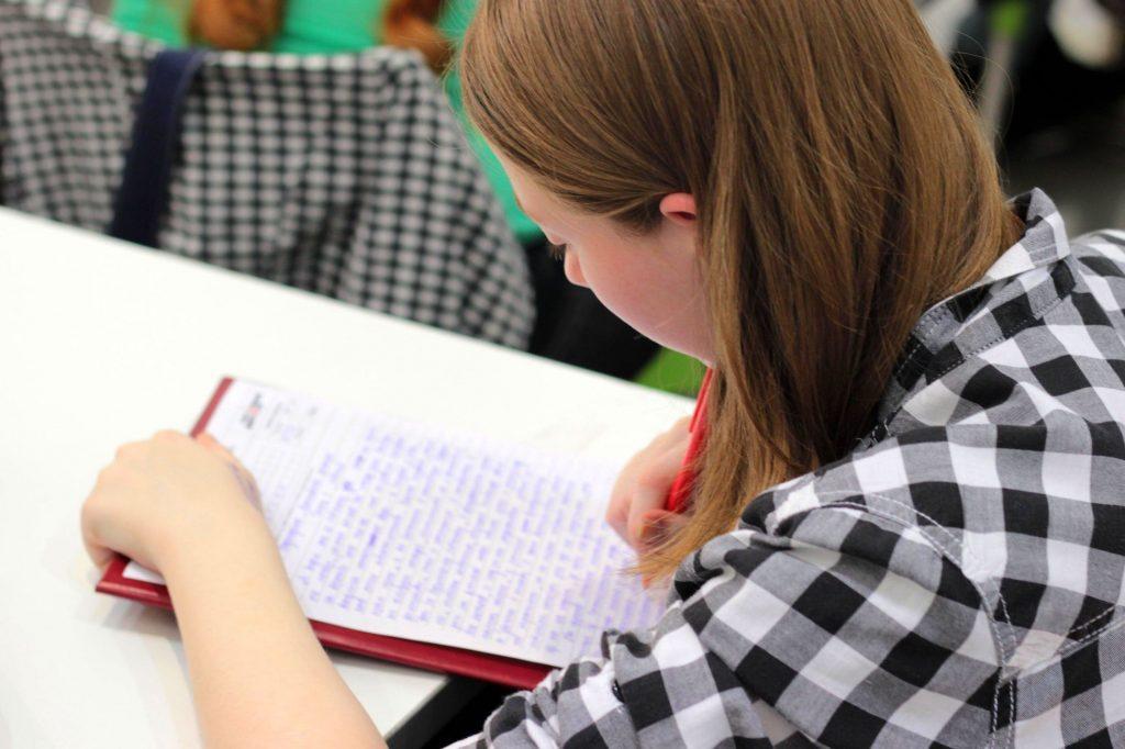 Jonge vrouw die tekst schrijft of examen aflegt